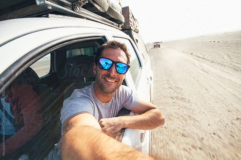 Man taking selfie while sitting in a car in motion on dirt road by Alejandro Moreno de Carlos for Stocksy United
