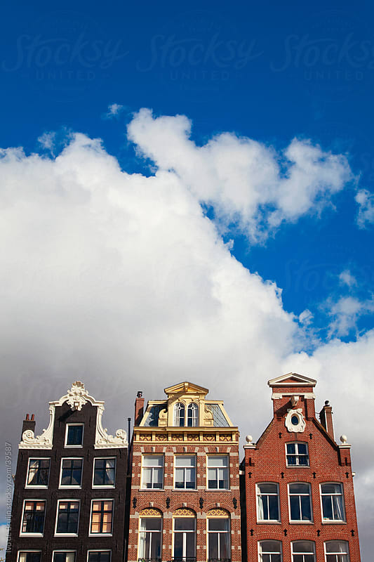 Facades of seventeenth century mansions in Amsterdam under a blue sky by Ivo de Bruijn for Stocksy United