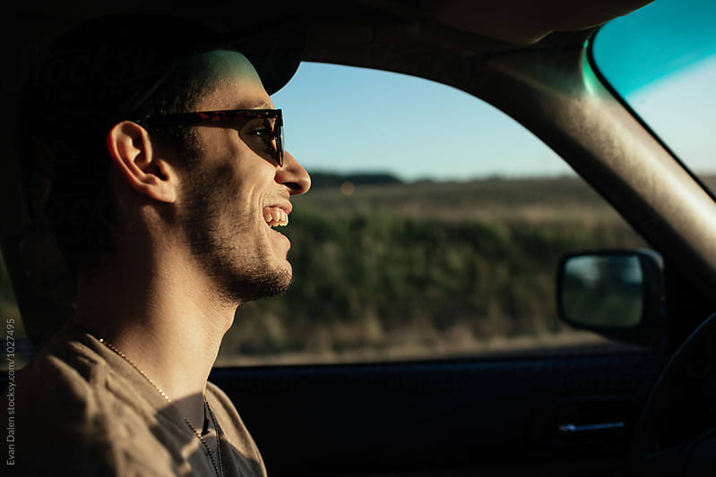 Man Driving Car Laughing  by Evan Dalen for Stocksy United