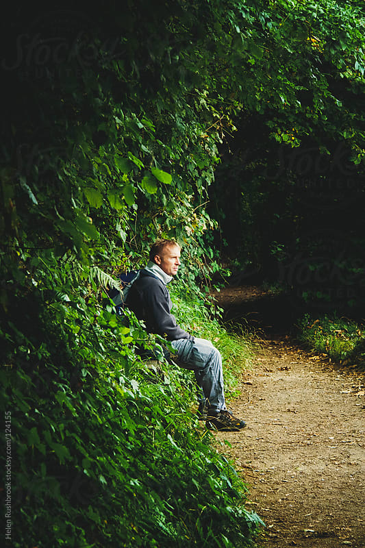 Man in outdoor wear sitting on a bench on a wooded footpath by Helen Rushbrook for Stocksy United