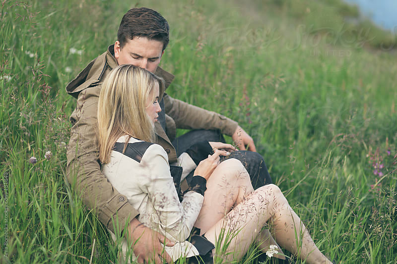 A man holding and kissing his partner sitting in tall grass by Ania Boniecka for Stocksy United
