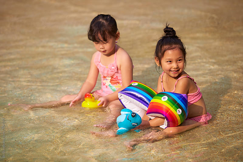 two lovely little asian girl sitting in the swimming pool by Bo Bo for Stocksy United