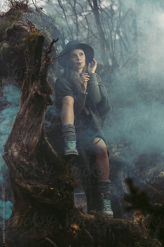 beautiful model on a overgrown root in colored foggy landscape by Leander Nardin for Stocksy United