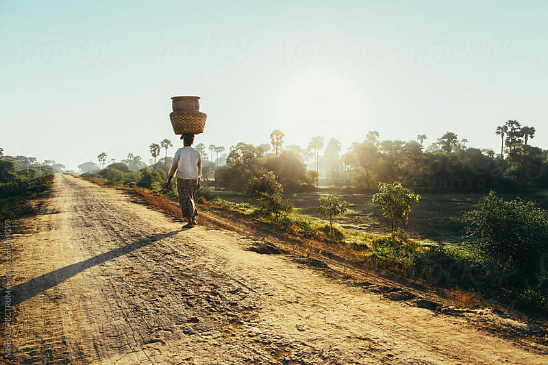 Woman Carrying Baskets on Head Walking in Burmese Countryside in Early Morning by VISUALSPECTRUM for Stocksy United