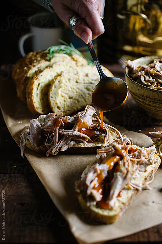 Pulled slow roasted pork sandwiches with barbecue sauce. by Darren Muir for Stocksy United