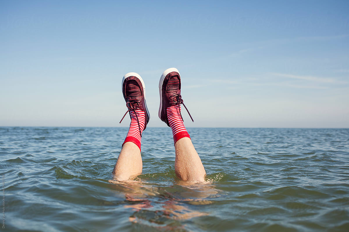 Legs sticking out of the water with wet shoes and socks. stocksy