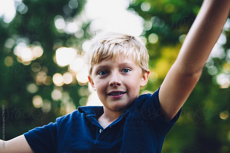 candid outdoor portrait of a boy  by Kelly Knox for Stocksy United