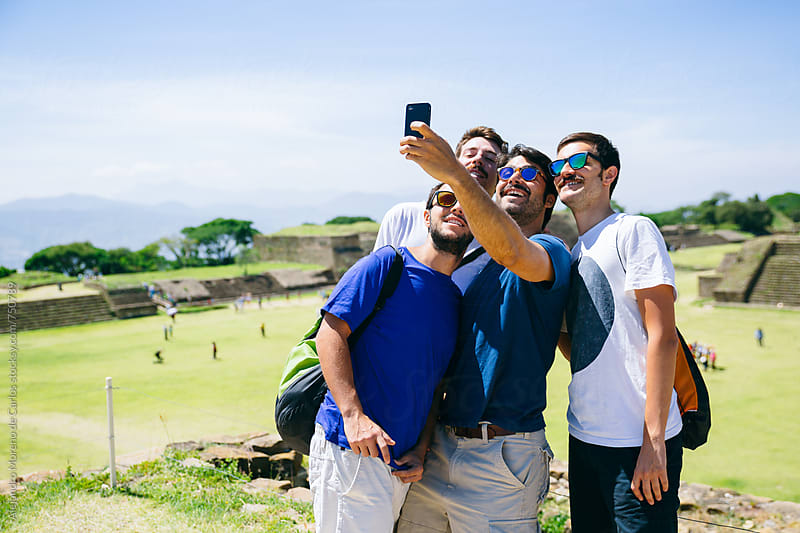Group of happy friends taking a self portrait of them in some ruins landmark while their vacation travel by Alejandro Moreno de Carlos for Stocksy United