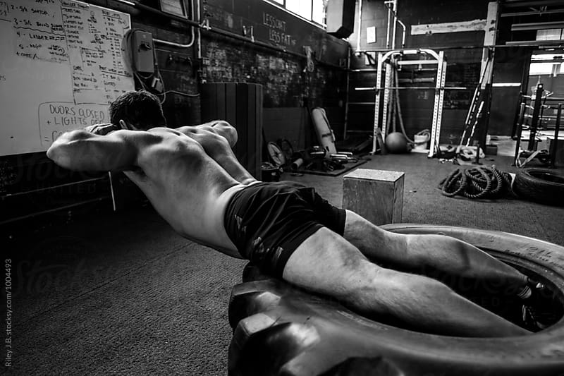 A muscular man doing a back exercise on a large tire by Riley Joseph for Stocksy United