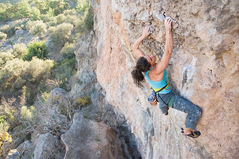 Woman rock climbing a difficult route outdoor by RG&B Images for Stocksy United