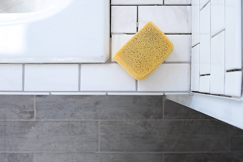 A sponge sits atop a newly tiled bathtub surround awaiting grout by Riley J.B. for Stocksy United