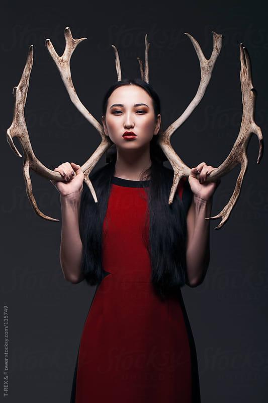 Portrait of Asian girl holding antlers by T-REX & Flower for Stocksy United