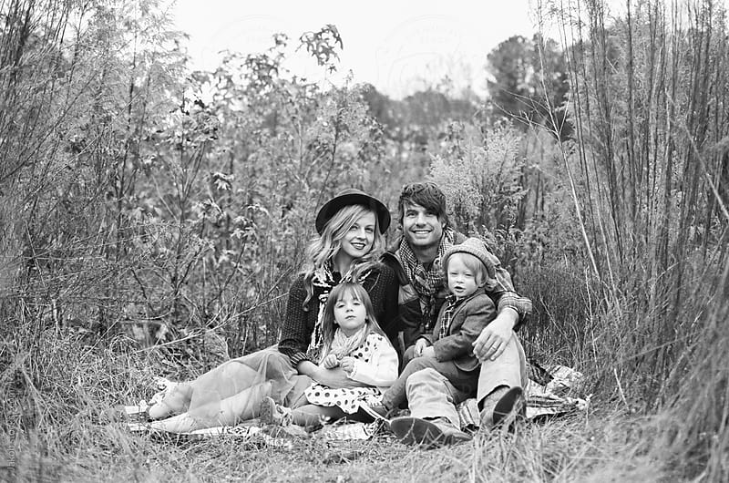 Beautiful family sitting in a field by Jakob for Stocksy United