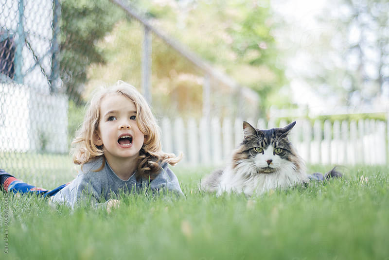 Child hangs out in his backyard with his cat by Cara Dolan for Stocksy United