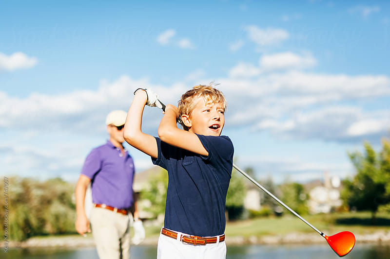 boy playing golf with his father in the background  by Kelly Knox for Stocksy United