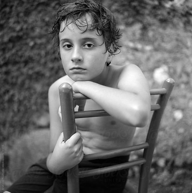 Young boy sitting on wooden chair by Bratislav Nadezdic for Stocksy United