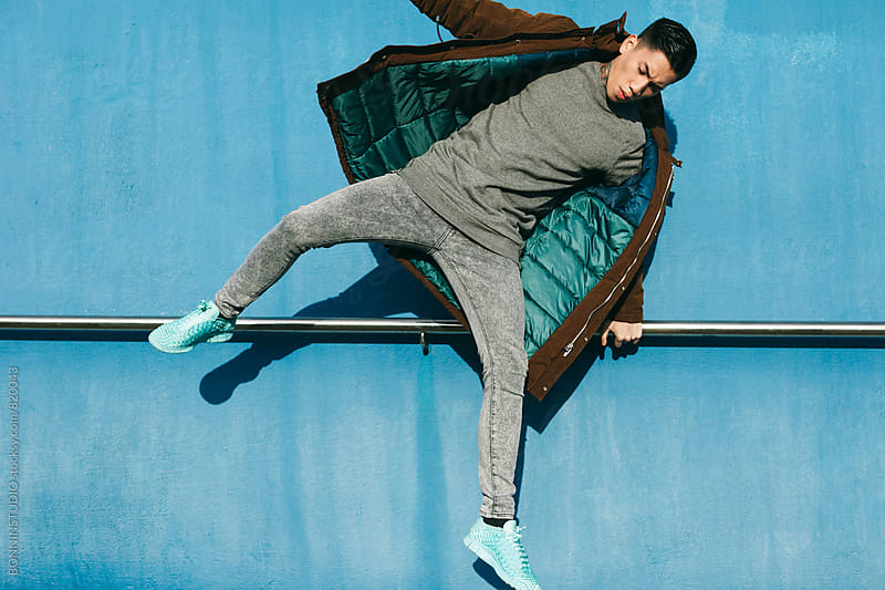 Asian modern man jumping in front of a blue wall. by BONNINSTUDIO for Stocksy United