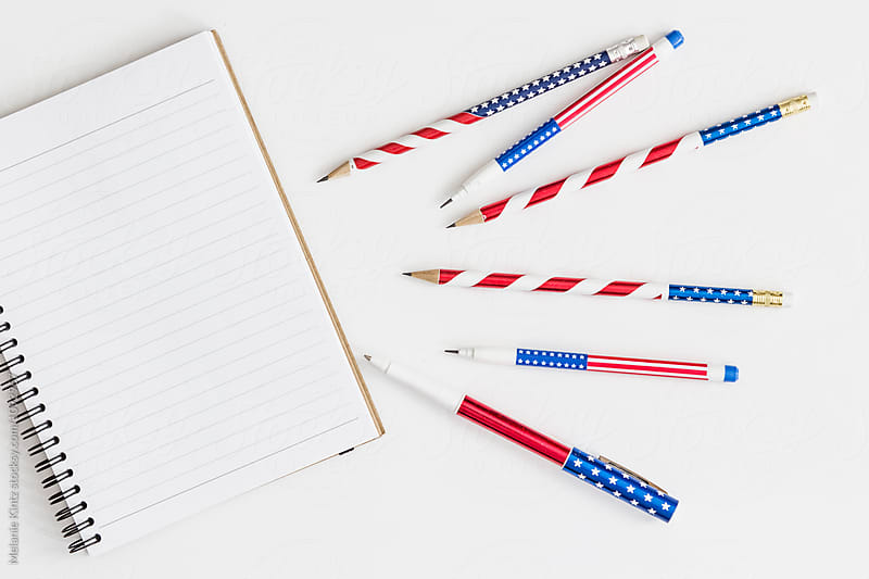 Open notebook and stars and stripes pens and pencils by Melanie Kintz for Stocksy United