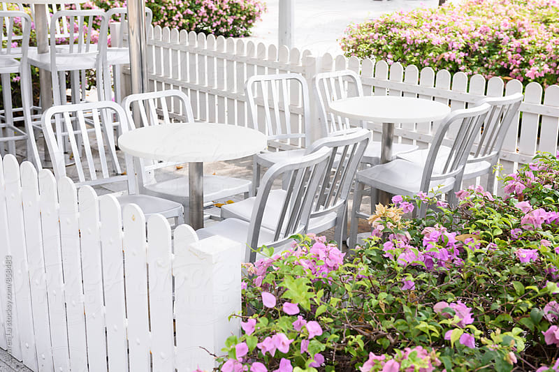 Restaurant outdoor seat beside white fence and flower bush by Lawren Lu for Stocksy United