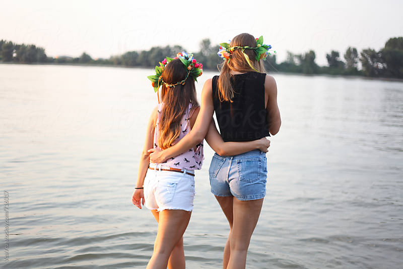 Two attractive woman hugging in the river from the back  by Marija Mandic for Stocksy United