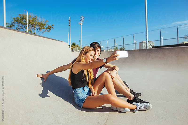 Teenage couple taking together a selfie on a skate park.  by BONNINSTUDIO for Stocksy United
