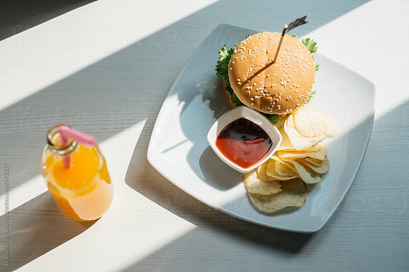 Burger served with chips and orange juice on the table by Brkati Krokodil for Stocksy United
