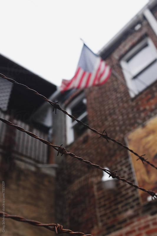 A barbed wire fence with an American flag waving in the background on a city building by Greg Schmigel for Stocksy United