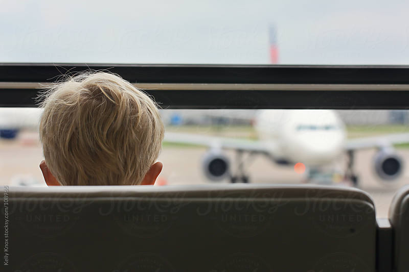 boy watches an airplane by Kelly Knox for Stocksy United