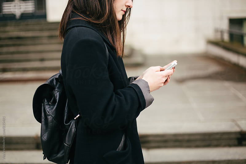 Woman browsing on mobile phone outdoors by VeaVea for Stocksy United
