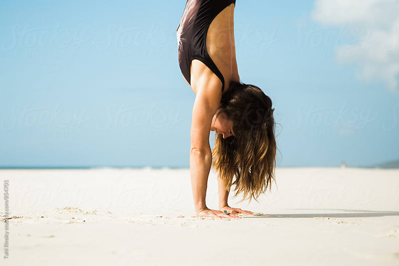 close up of women in handstand on empty beach by Tahl Rinsky for Stocksy United
