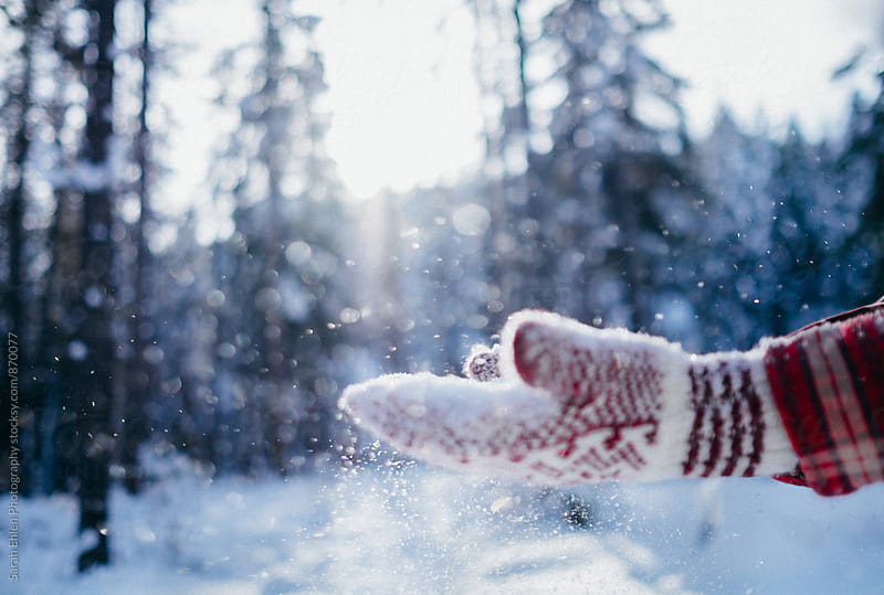 Person playing in the snow with red mittens on by Sarah Ehlen Photography for Stocksy United