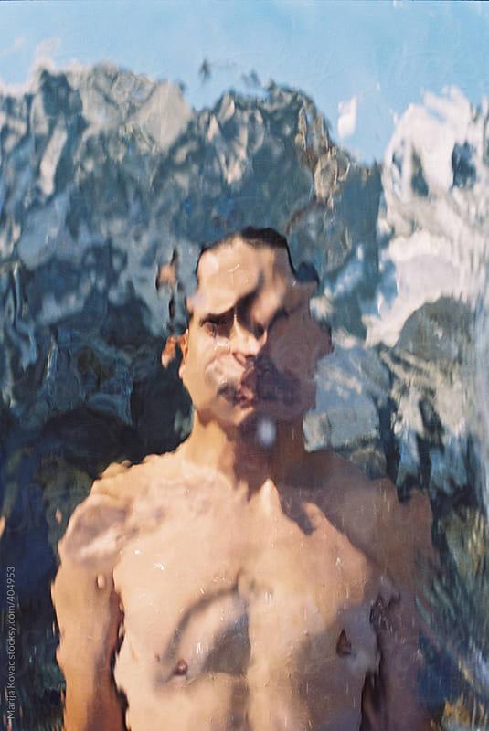 Boy behind the waterfall by Marija Kovac for Stocksy United