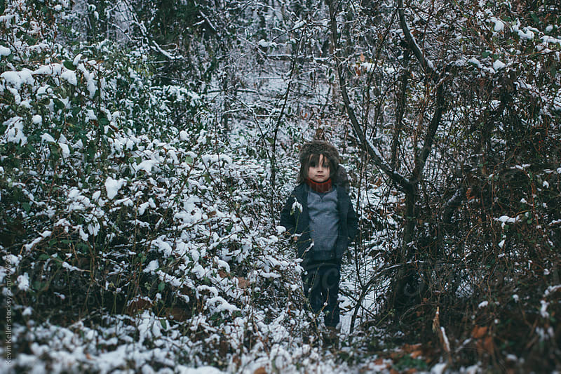 Young Boy Standing in Snow Covered Trees by Kevin Keller for Stocksy United