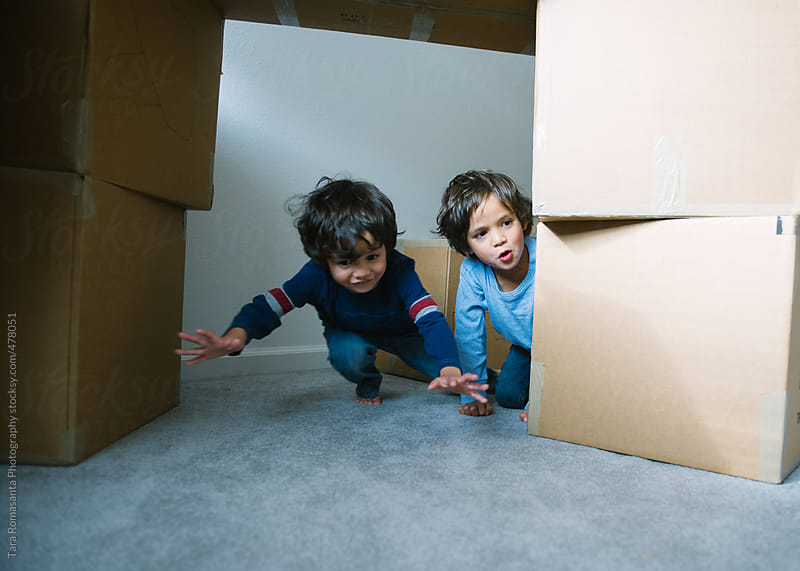 brothers play amidst towers of moving boxes by Tara Romasanta for Stocksy United