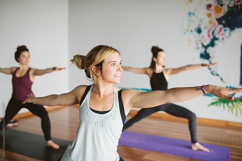 Students in a yoga class holding vinyasa poses. by Kate Daigneault for Stocksy United