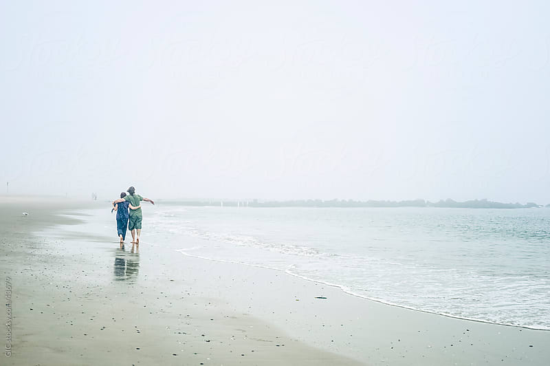 Couple walking on the beach by WAVE for Stocksy United