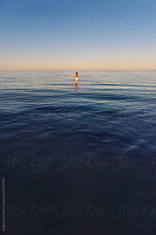 Girl with outstretched arms at the beach at sunset by Angela Lumsden for Stocksy United