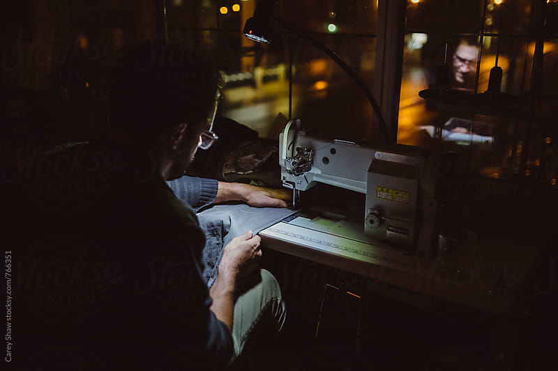 Evening portrait of male sewing in downtown workspace by Carey Shaw for Stocksy United