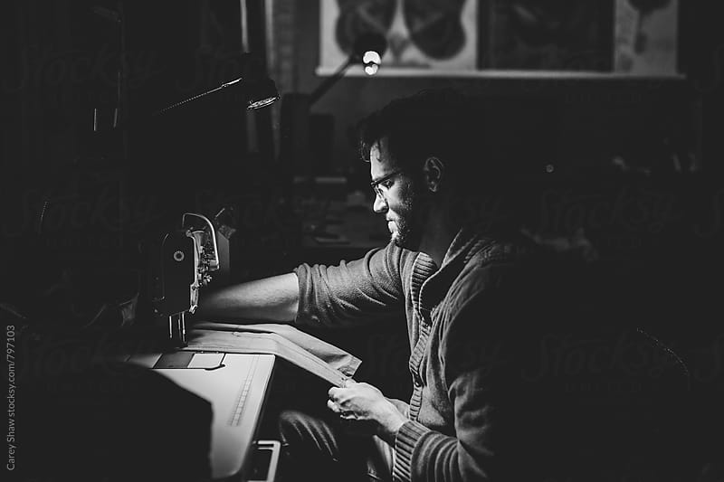 Black and white portrait of man sewing by Carey Shaw for Stocksy United