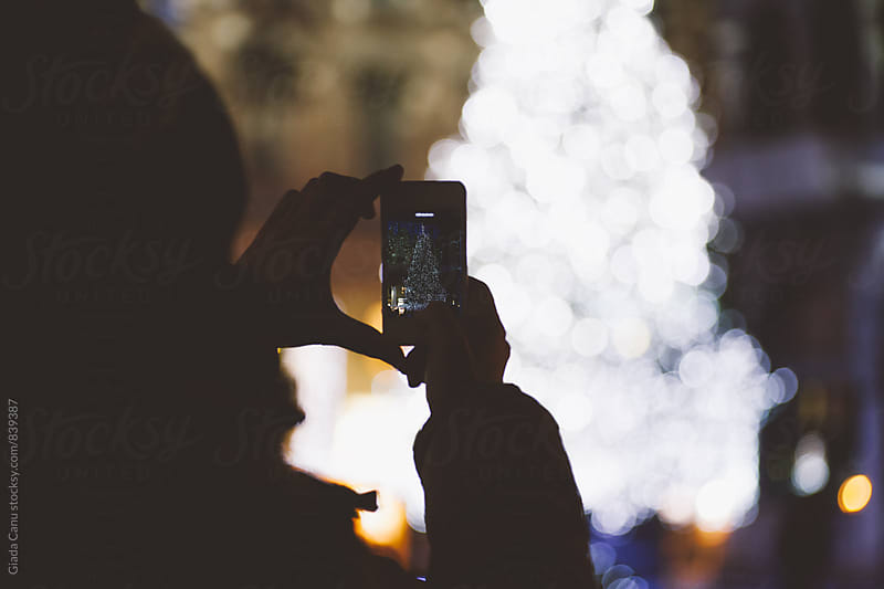 Taking a picture of a christmas tree by Giada Canu for Stocksy United