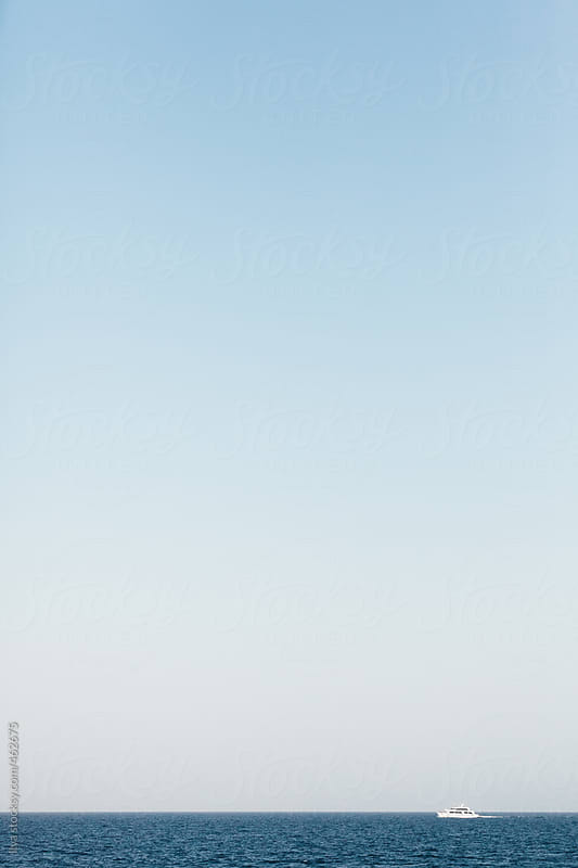 White distant cruise ship sailing on the Red Sea with copyspace on sky by Ilya for Stocksy United