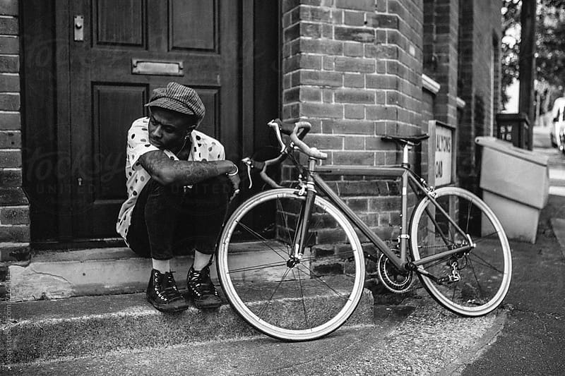 Stylish man sitting on a step next to his push bike. by kkgas for Stocksy United