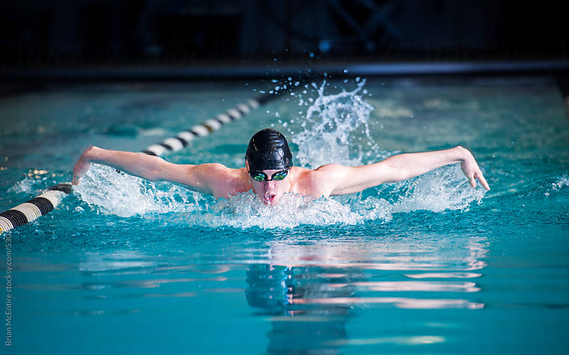 Male Swimmer Racing Toward Finish Performing Butterfly Stroke by Brian McEntire for Stocksy United