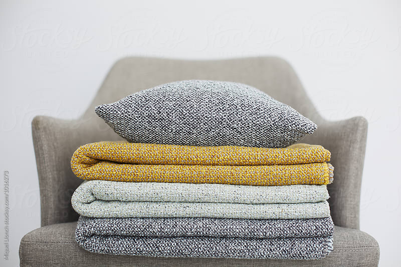 Set of folded blankets and pillow on a chair by Miquel Llonch for Stocksy United