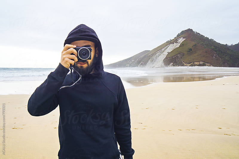 Hooded man taking a photo on the beach by ACALU Studio for Stocksy United