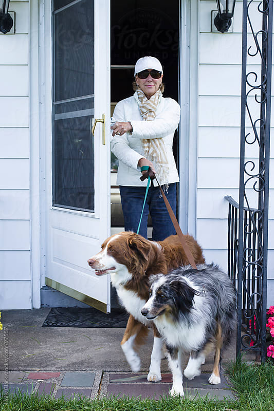 A woman walks her dogs out the front door to her home. by Holly Clark for Stocksy United