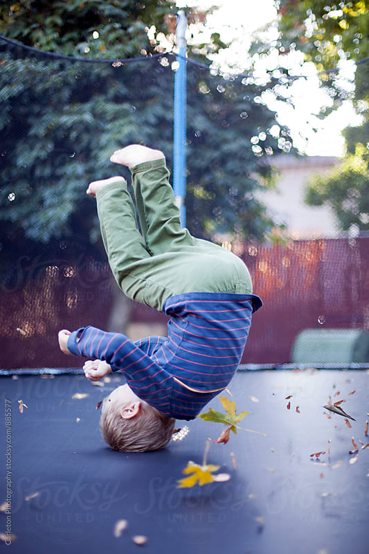 Boy flipping on backyard trampoline by Carleton Photography for Stocksy United