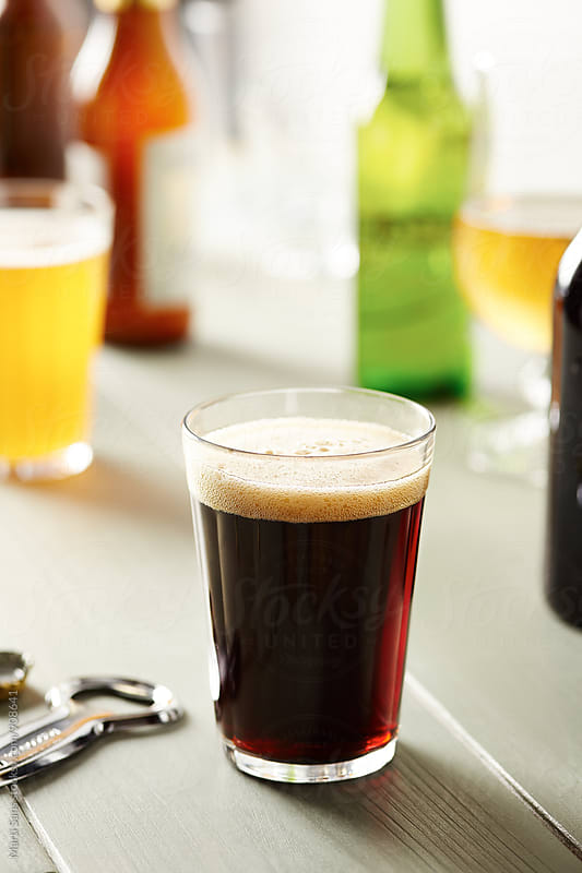 Dark beer with foam in glass by Martí Sans for Stocksy United