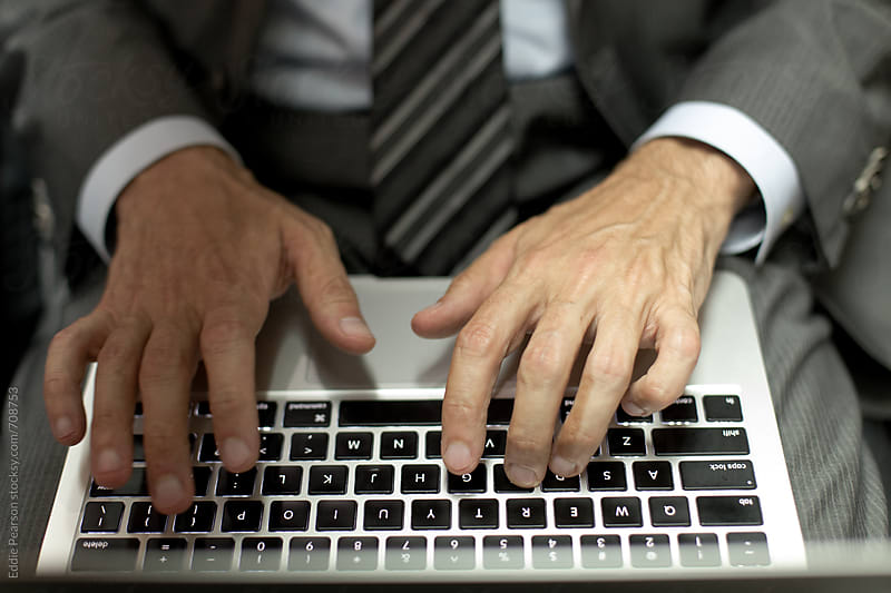 Closeup shot of a business man typing on his laptop by Eddie Pearson for Stocksy United