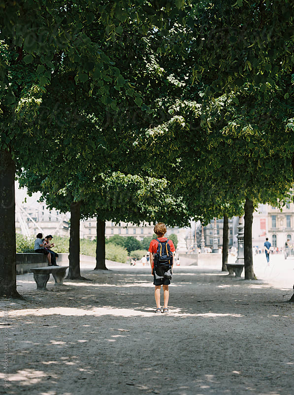 Rear view of boy standing under trees in Paris, France by Kirstin Mckee for Stocksy United
